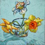 Three spring jonquils in a blue rimmed glass